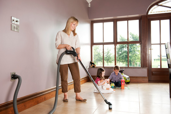 Woman uses central vacuum system
