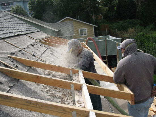 Blowing cellulose into the Larsen Truss space added to the outside of the old exterior walls