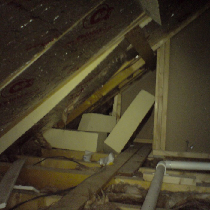 Loft space of a new house showing insulation that has fallen out because it wasn't installed to manufacturer's specification.