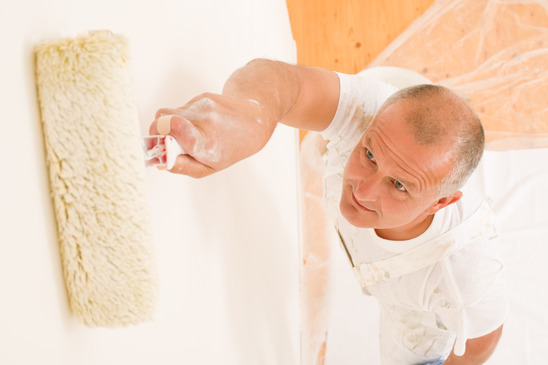 Home decorating mature man painting wall roller