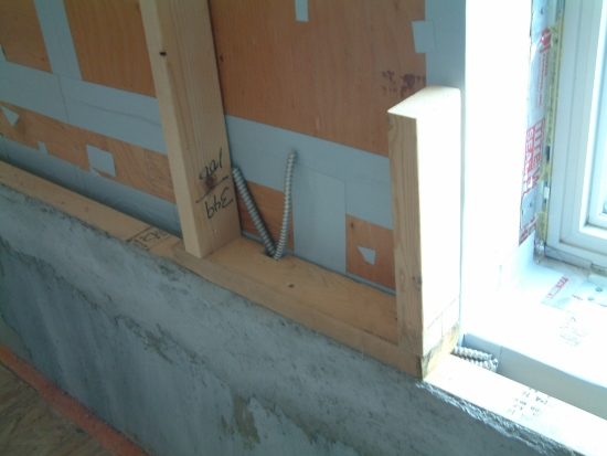 A mock-up of the 2x4 wall framing on the interior of the plywood air barrier (which has grey tape sealing cracks and fastener holes) shows how the electrical wiring can run in the thermal break in the wood sill plate to get by the picture window.
